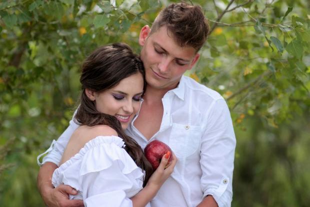юноша в белой рубашке обнимает девушку с красным яблоком в руке