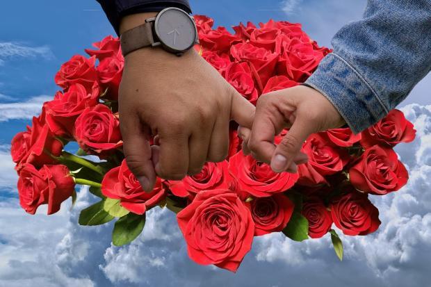 пара держится на руки на фоне букета из красных роз