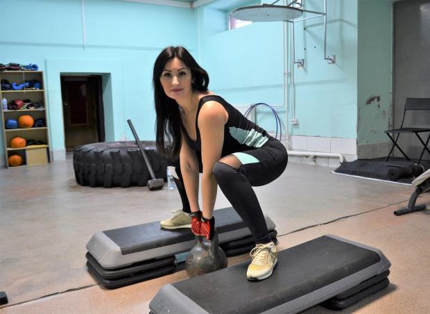 девушка в спортзале с гирей