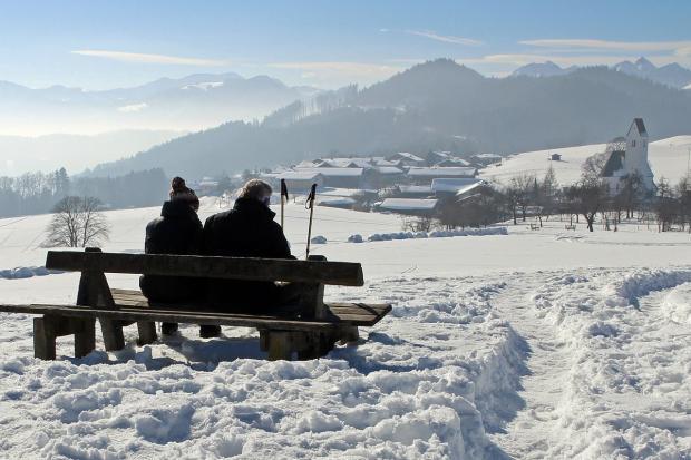 двое смотрят на горы на деревянной скамейке в снегу