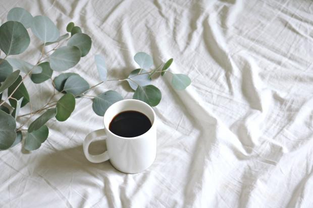 чашка кофе на белой простыне