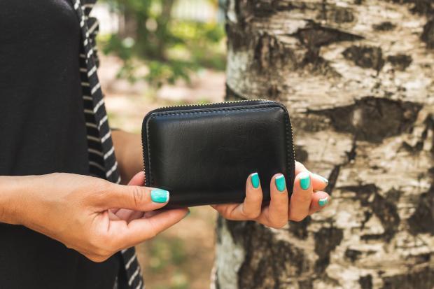 Черный кошелек в женских руках
