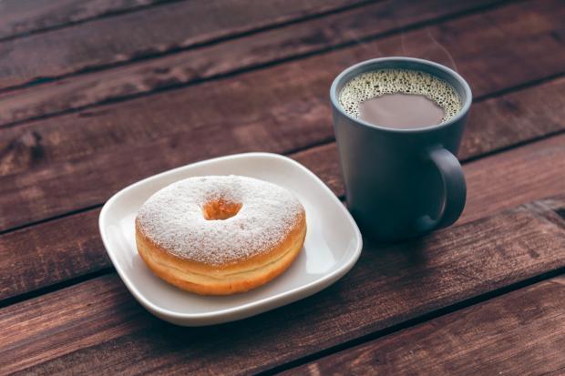 Пончик на белой тарелке и кофе в темной чашке