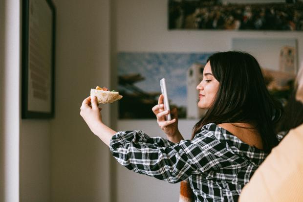 Девушка в клетчатой рубашке фотографирует еду телефоном