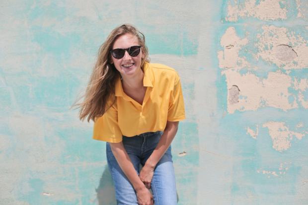 Светловолосая девушка в желтой блузе и голубых джинсах