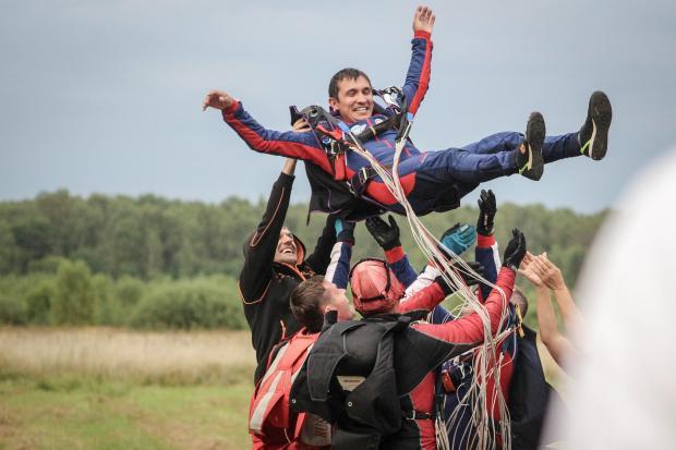 люди люди подбрасывают мужчину с парашютом на руках