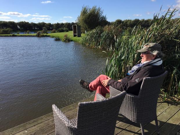 мужчина сидит на берегу реки в кресле