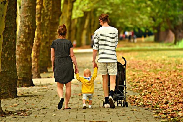 семейная пара гуляет с ребенком по аллее с деревьями