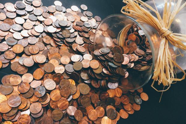 Монеты рассыпанные на столе и стеклянная банка