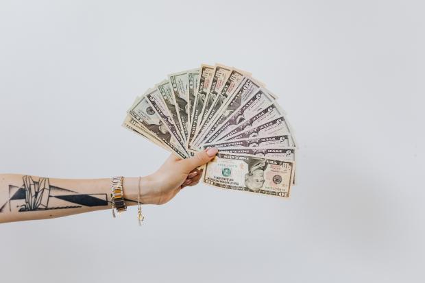 женская рука с татуировками держит деньги