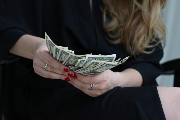 пачка долларов в руках у девушки в черном платье