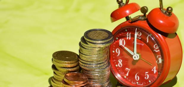 красный механический будильник стоит рядом со стопками монет