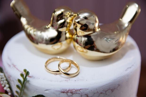 сувениры в виде двух птичек и два обручальных кольца на белой скатерти