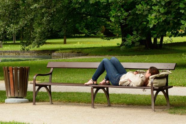 девушка лежит на скамейке в парке