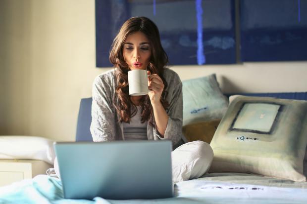 девушка работает за компьютером и пьет кофе