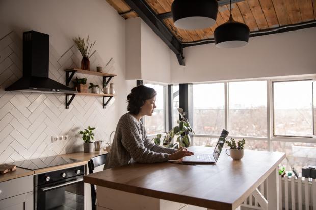 девушка работает за ноутбуком в кухне