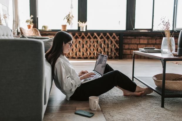 девушка сидит на полу с ноутбуком
