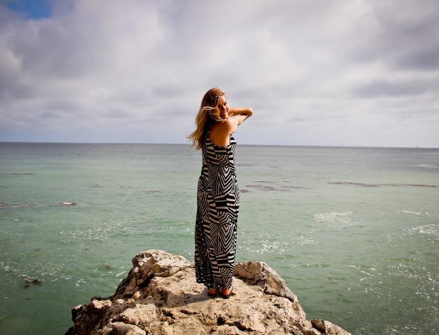 девушка стоит на краю скалы у моря