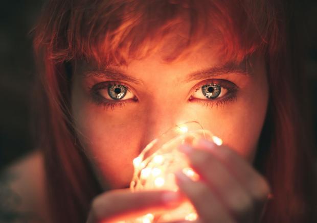 Девушка со светящейся гирляндой перед лицом