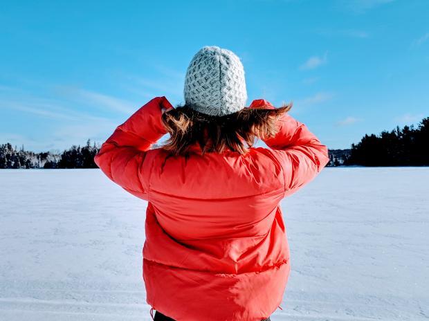 Девушка в красной куртке и светлой шапке стоит на снегу