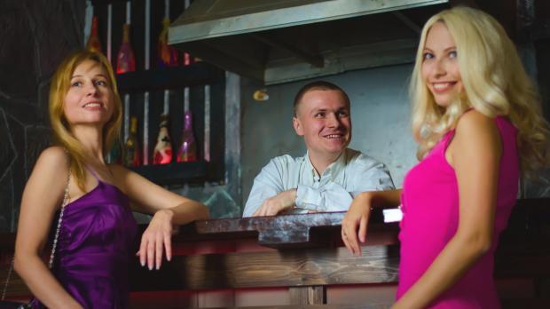 две девушки в баре, бармен