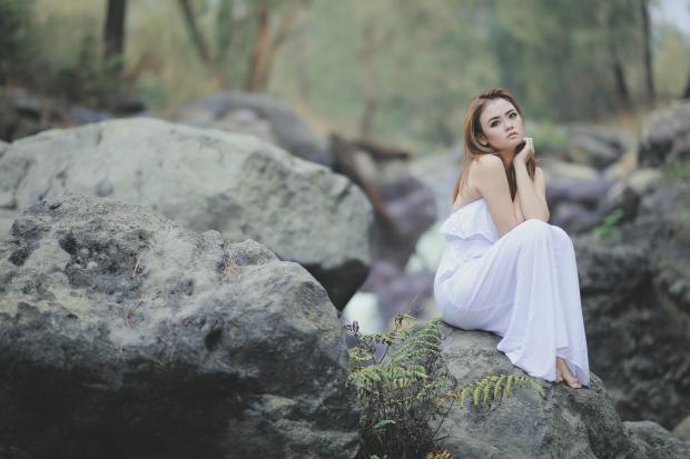 девушка в белом платье сидит на камне