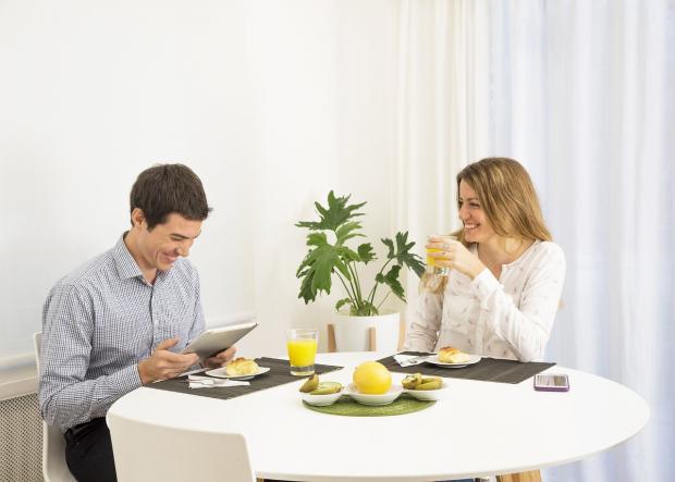 мужчина с девушкой смеются за чайным столом