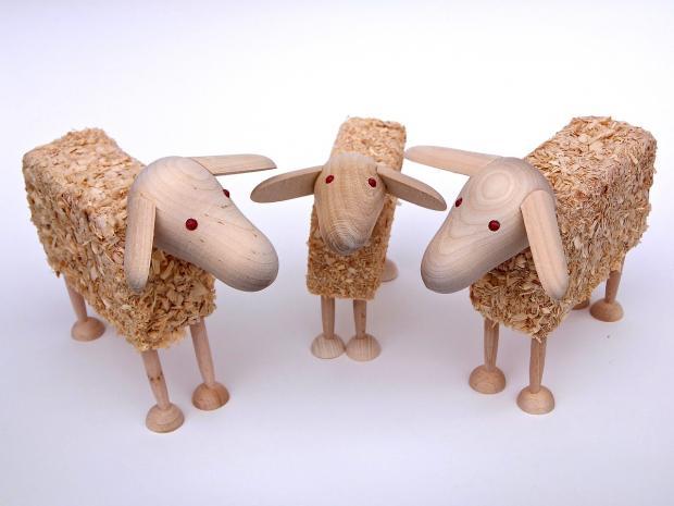 стоят три деревянных игрушки овечки