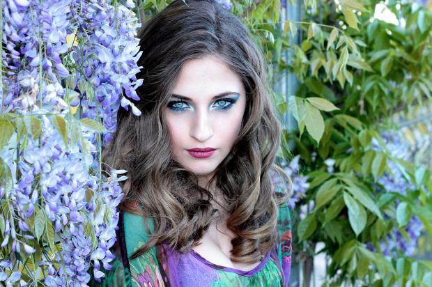 голубоглазая девушка стоит в саду
