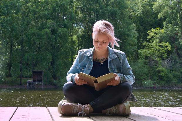девушка на пирсе сидит и читает книгу