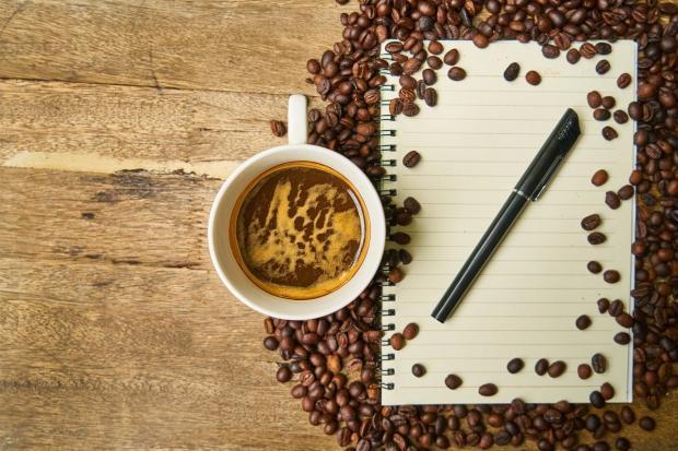 среди рассыпанных зерен кофе стоит чашка и лежит блокнот с ручкой