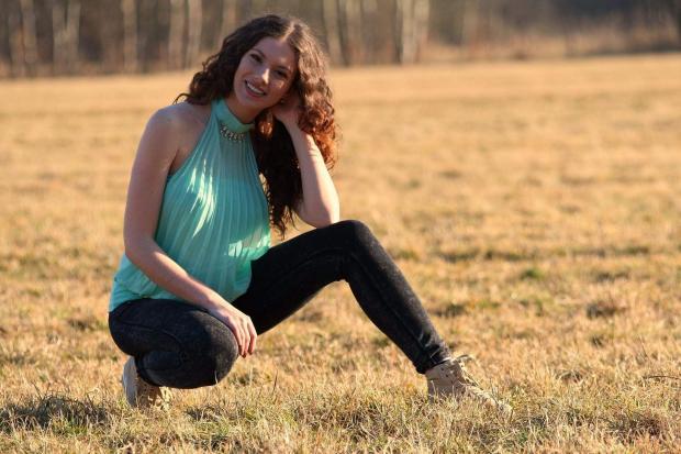 девушка с длинными вьющимися  волосами на поле