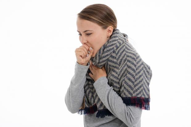 девушка замотанная в шарф кашляет
