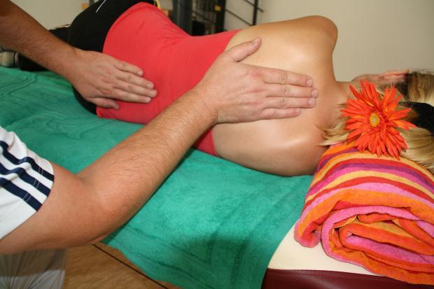 мануальный терапевт обследует спину девушки