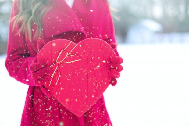 девушка в красном пальто держит в руках большое сердце