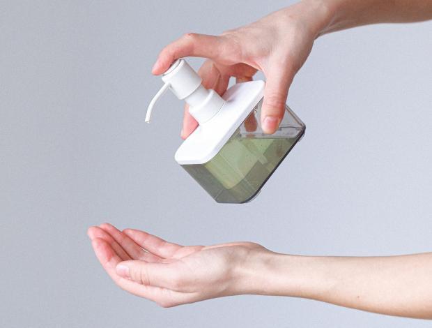 Бутылка с жидким мылом в женских руках