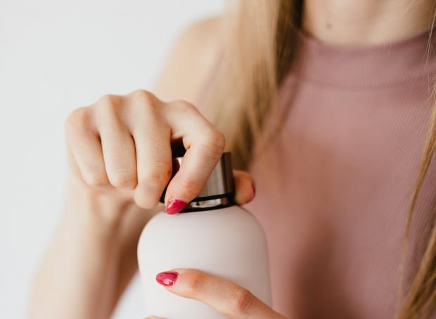 Девушка держит в руках бутылку с жидким гелем