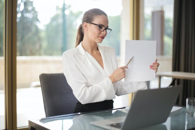 девушка с бумагами сидит перед ноутбуком
