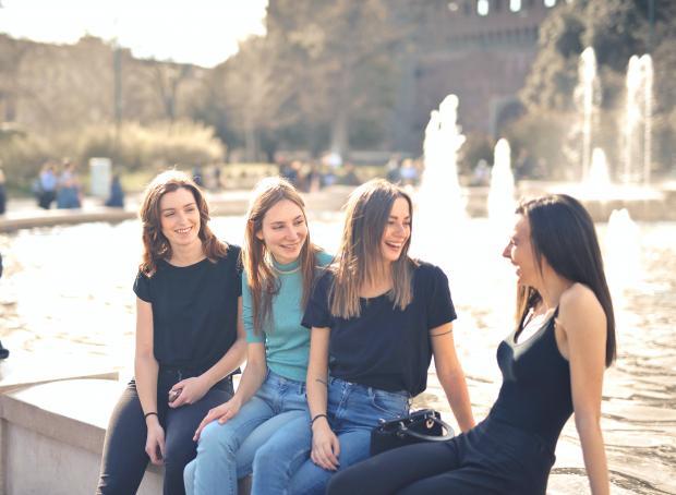 четыре девушки сидят возле фонтана