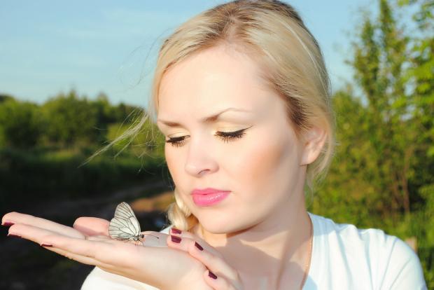 девушка держит на ладони бабочку