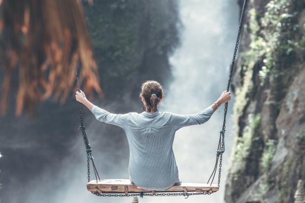 девушка сидит на качели в горах