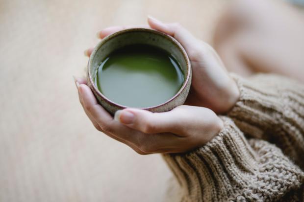 чашка с зеленым чаем в руках