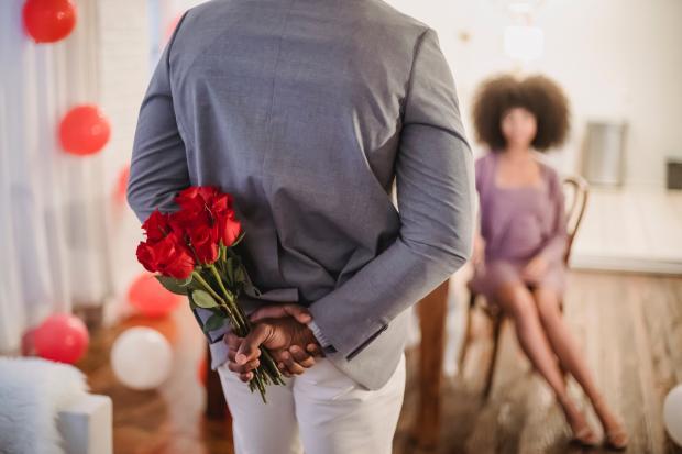Мужчина держит цветы за спиной