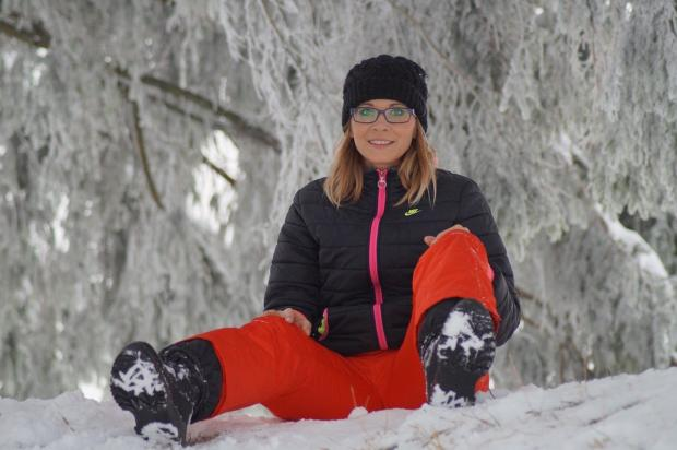 девушка в спортивном костюме сидит на снегу