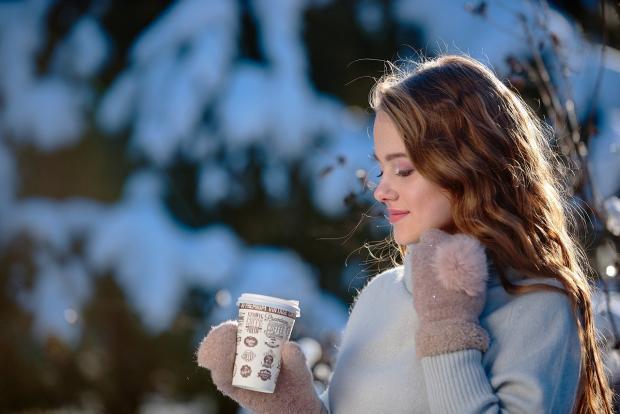 девушка с распущенными волосами пьет кофе в зимнем лесу