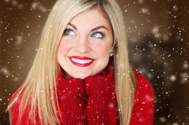 блондинка в красном свитере улыбается