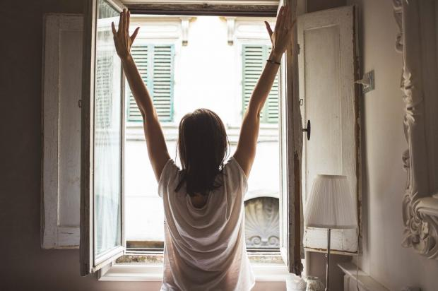 девушка потягивается у раскрытого окна