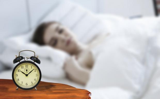стоит будильник на прикроватной тумбочке