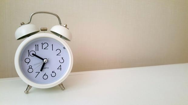 белый будильник стоит на столе