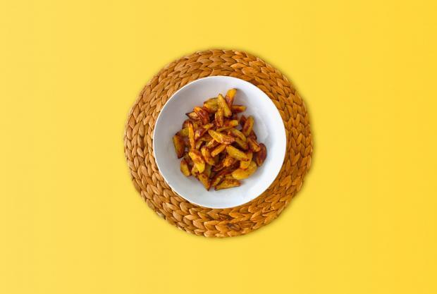 тарелка с жареной картошкой на желтом столе